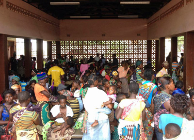 African mothers wait with their infants to receive health services.