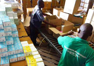 Two men packaging malaria commodities to be distributed to health centers and community health workers