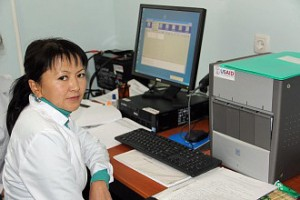 A female Kyrgyz lab technician sitting in front of a computer monitor and printer