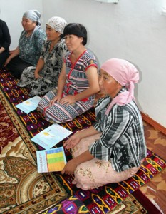 Four Kyrgyz women sit cross-legged on the floor learning about tuberculosis symptoms