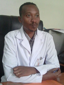 Male Ethiopian health professional sitting at desk.