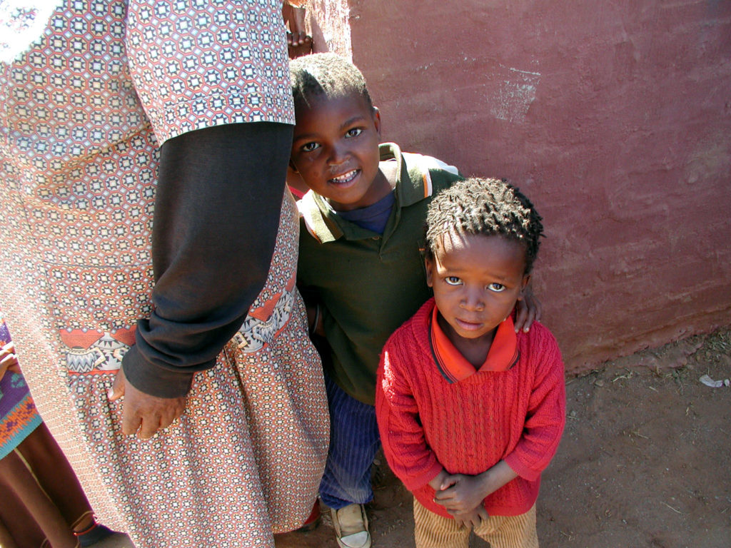 Two young boys who have lost parents stand next to a community worker in South Africa. © 2003 Melissa May, Courtesy of Photoshare