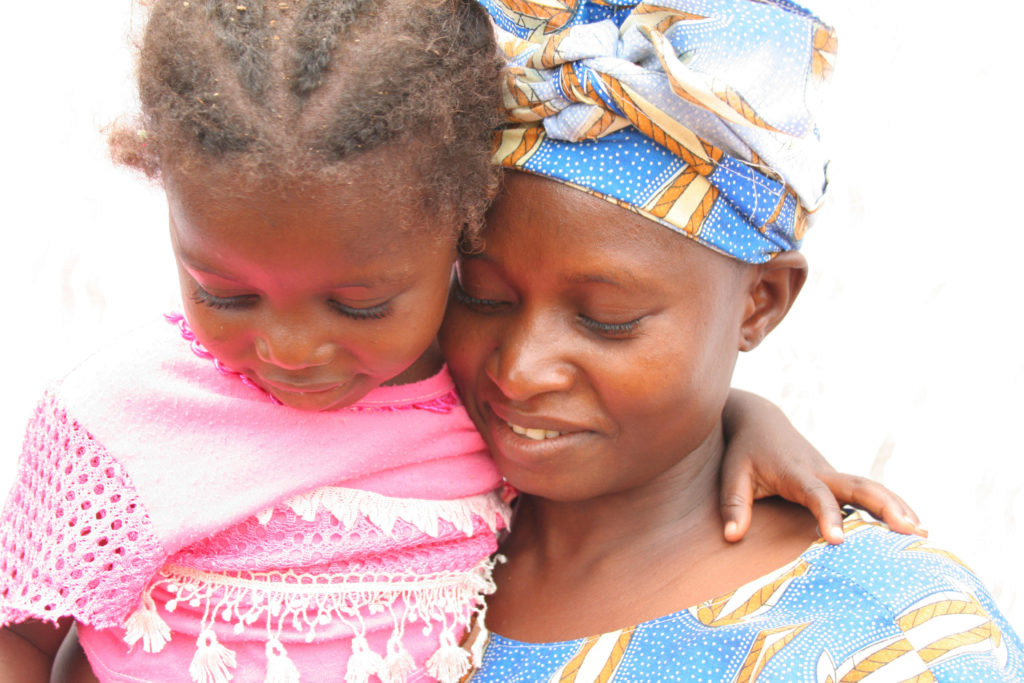 Un agent de santé communautaire tient sa fille au cours d'une visite à la maison chez un voisin pour l'éducation sanitaire au Mali rural. © 2008 Caitlin Cohen, avec la permission de Photoshare